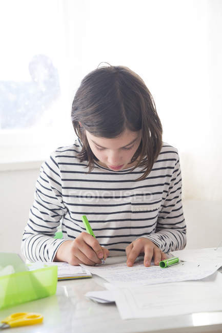 Focused girl doing homework at desk at home — Stock Photo