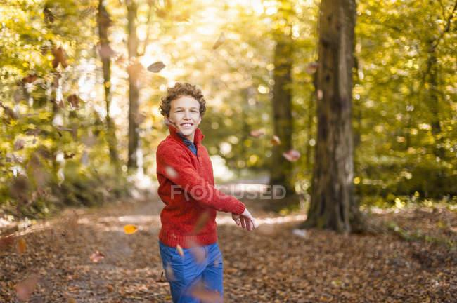 Garçon souriant jetant des feuilles dans l'air dans la forêt automnale — Photo de stock
