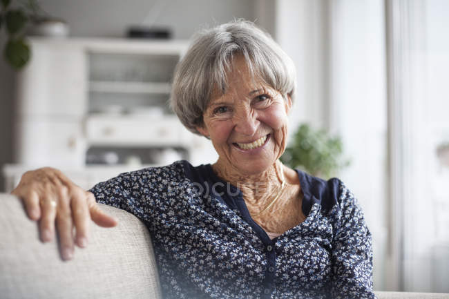 Portrait of happy senior woman sitting on couch at home — Stock Photo
