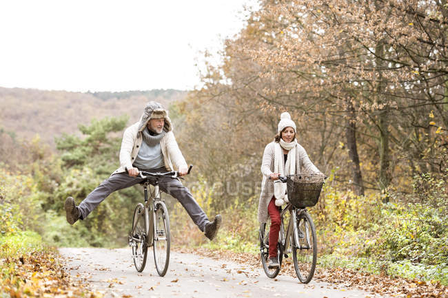 Senior couple doing a bicycle trip with dog in autumn — Stock Photo