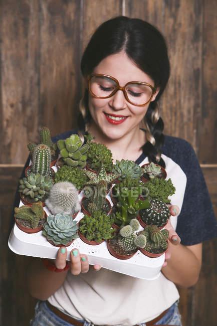 Hipster junge Frau mit Tablett Kakteen und Sukkulenten — Stockfoto