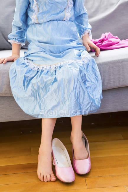 Little girl dressed up as princess trying on lady shoes — Stock Photo