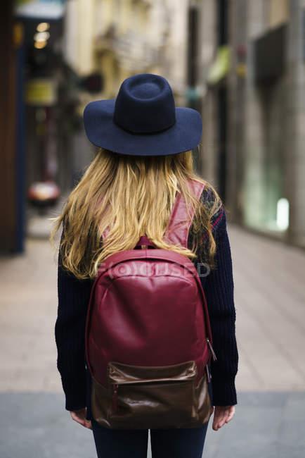Vista posteriore del turista con lo zaino blu cappello rosso — Foto stock