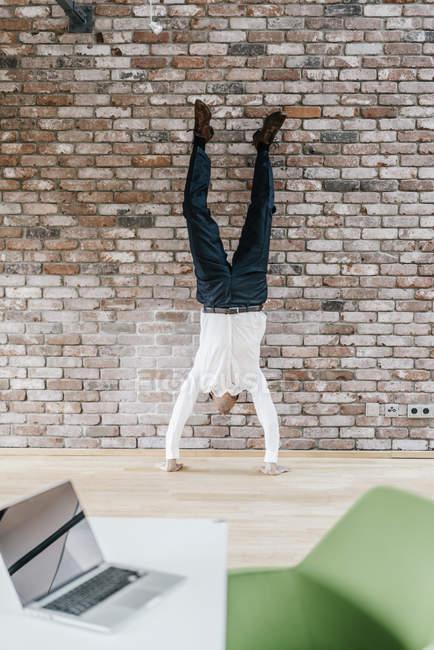 Бизнесмен делает стойку на руках перед кирпичной стеной — стоковое фото