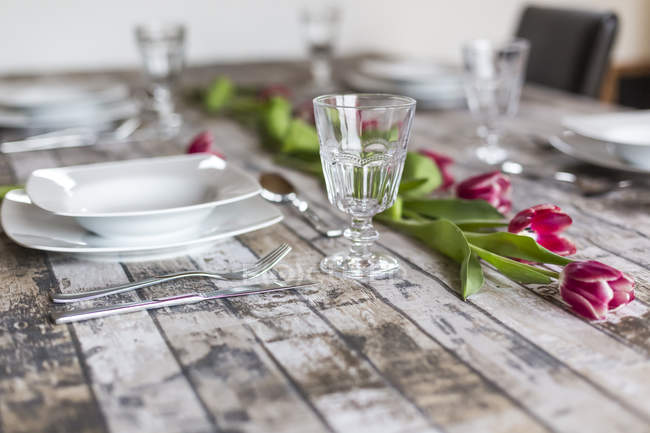 Vista de cerca de la mesa de madera servida con vajilla y flores - foto de stock