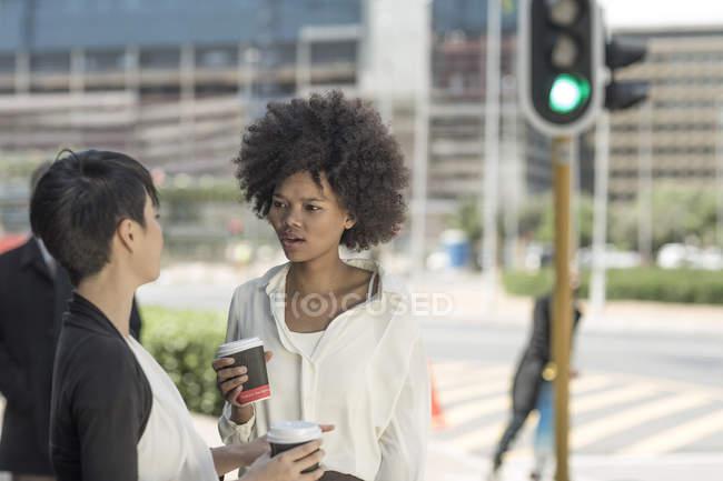 Дві жінки на вулицях міста, пити каву і говорити — стокове фото