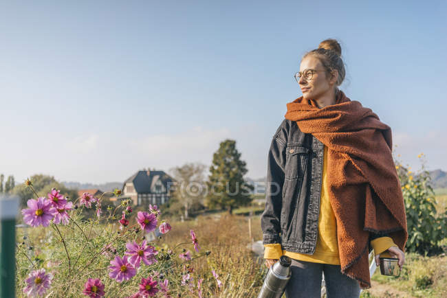 Young woman with thermos flask standing in cottage garden — Stock Photo