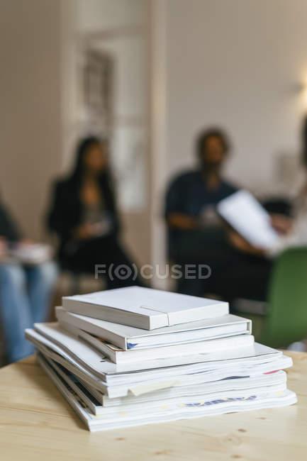 Pile of magazines and books on shelf, business peole talking in background — Stock Photo