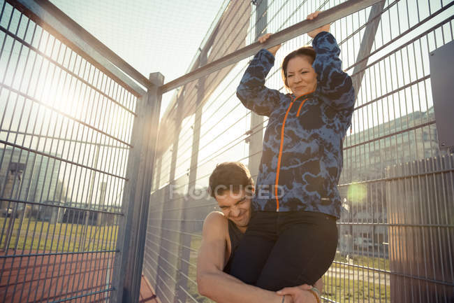 Young man helping girlfriend doing chin-ups — Stock Photo