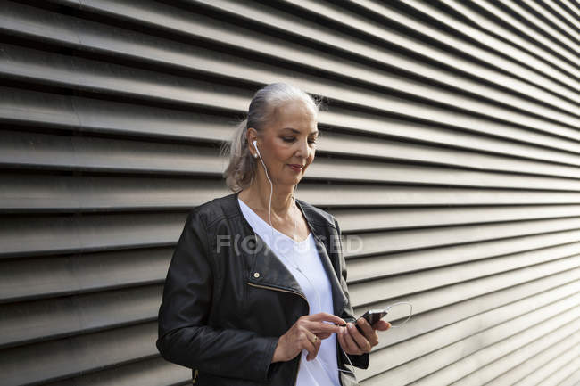 Woman listening music with earphones and smartphone — Stock Photo