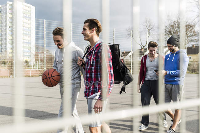 Young men walking on basketball court — Stock Photo