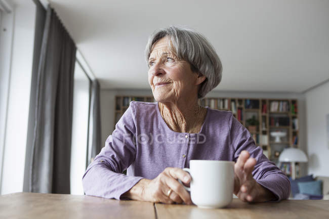 Portrait of senior woman sitting at table with cup of coffee looking through window — Stock Photo