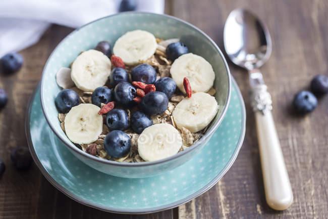 Чаша черничного мюсли с волчьей ягодой и банановыми ломтиками — стоковое фото