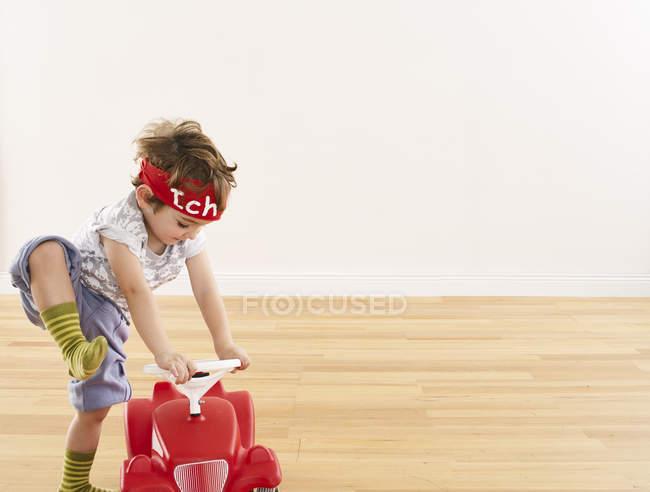 Menina brincando com o carro pedal — Fotografia de Stock