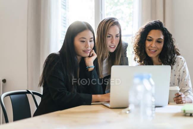 Três mulheres de negócios trabalhando juntas no laptop — Fotografia de Stock