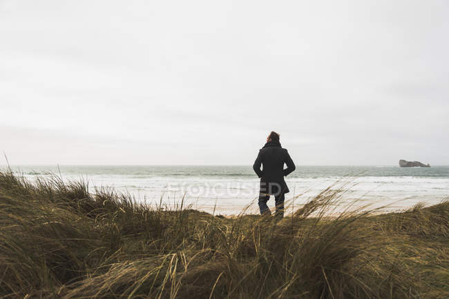 Man standing at the coast with cloudy sky — Stock Photo