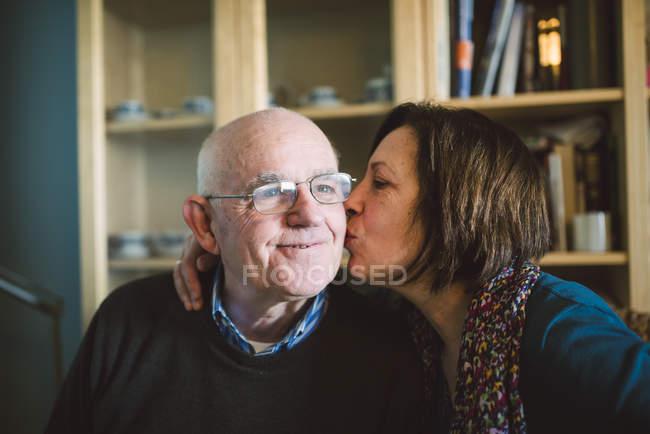 Senior mujer besos a marido en casa - foto de stock