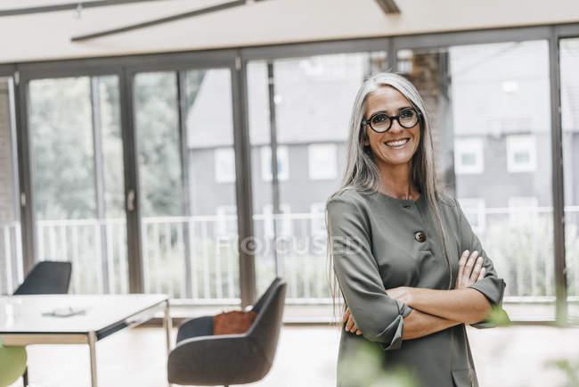 Ritratto di donna sorridente con lunghi capelli grigi in piedi in ufficio — Foto stock