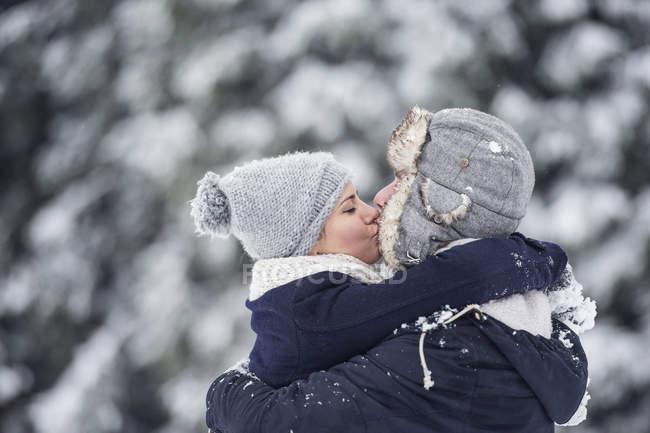 Пара поцелуев зимой на размытом фоне — стоковое фото