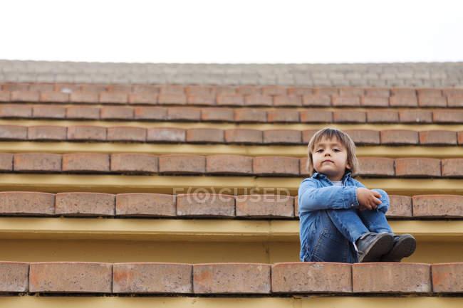 Porträt eines kleinen Jungen auf den Stufen eines Freilichttheaters — Stockfoto