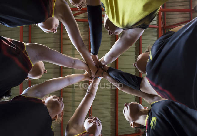 Female volleyball team huddling and stacking hands — Stock Photo