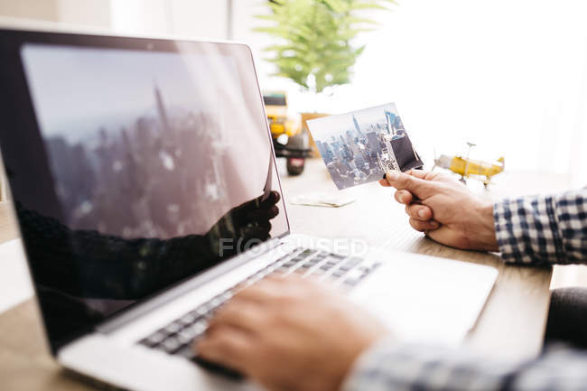 Young man planning his next journey, using laptop, holding photography — Stock Photo