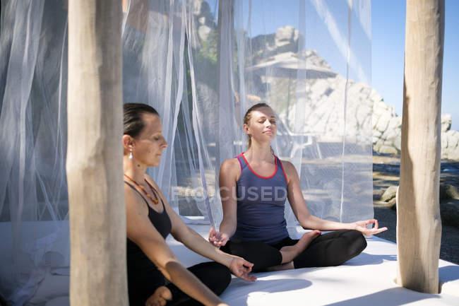 Deux femmes pratiquant la méditation de yoga dans une cabane — Photo de stock