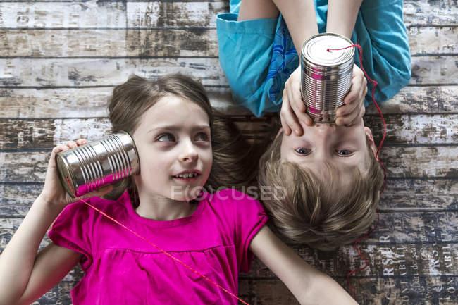 Портрет мальчика и девочки, играющих с жестяным телефоном — стоковое фото