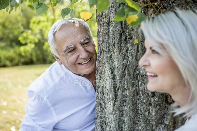 Улыбающаяся пожилая пара, стоящая у дерева — стоковое фото