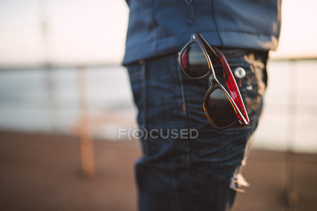 Sunglasses hanging out of trouser pocket — Stock Photo