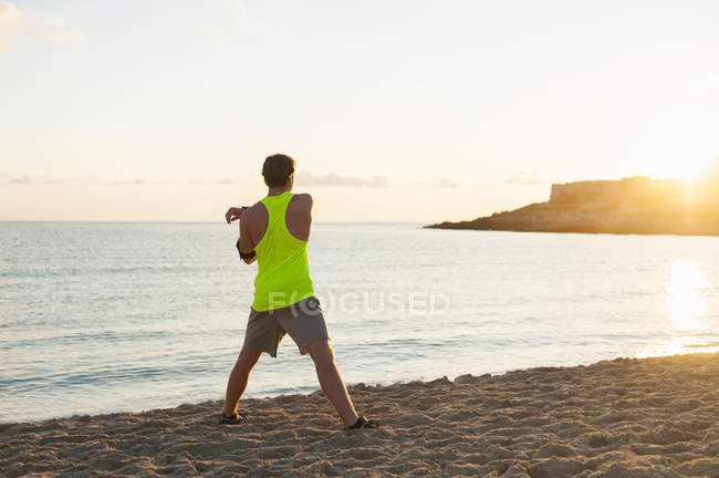 Бігун розтягування на піщаному пляжі у ранок — стокове фото