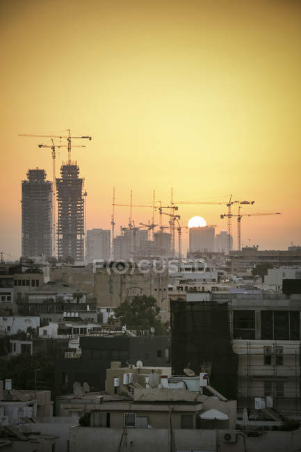 Israel, Tel Aviv, cityscape with cranes at sunset — Stock Photo