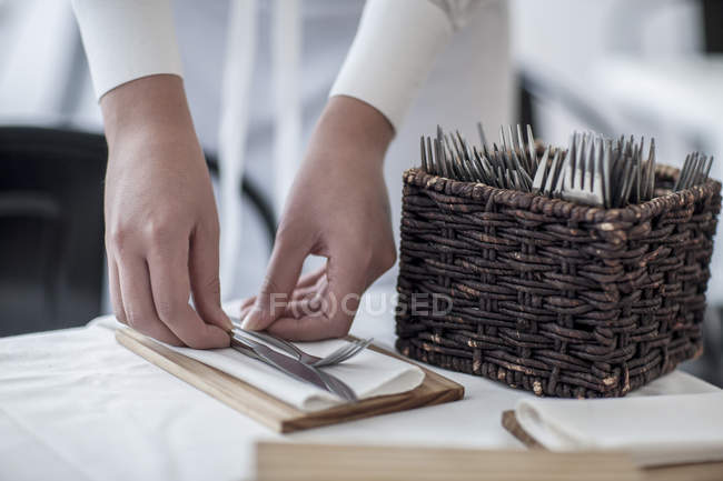 Person placing cutlery on restaurant tabel — Stock Photo