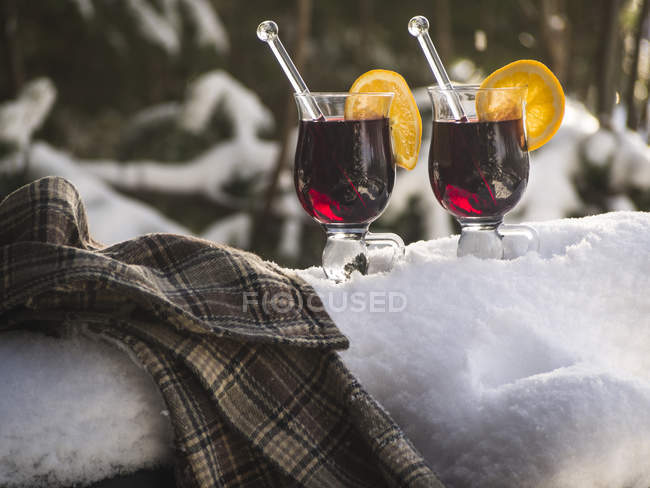 Glasses of mulled wine in snow outdoors — Stock Photo
