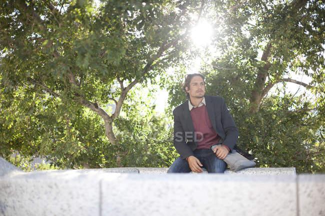 Человек сидит в парке в солнечный день — стоковое фото