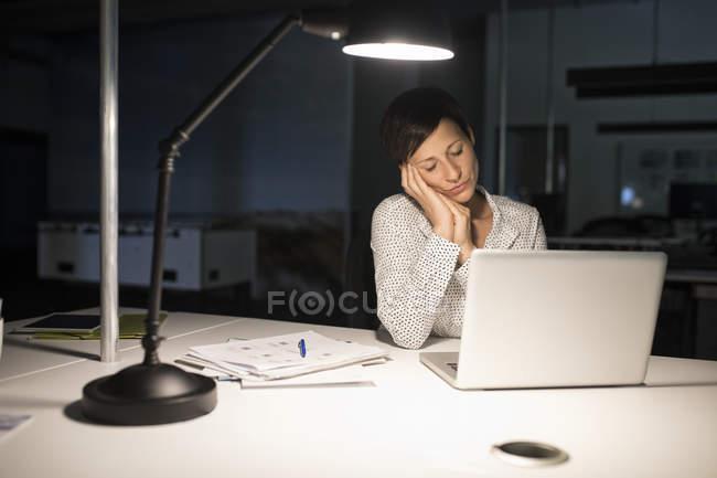 Mulher de negócios exausto, sentado no escritório com o laptop no escuro — Fotografia de Stock