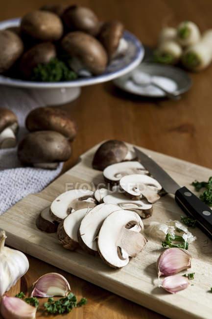 Knoblauchzehen, in Scheiben geschnittene Portobello-Pilze, Petersilie und Küche Messer auf Holzbrett — Stockfoto