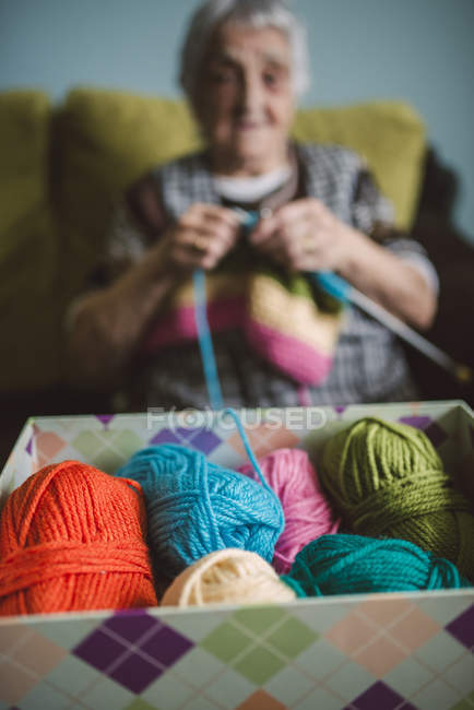 Box of different balls of wool, senior woman background — Stock Photo