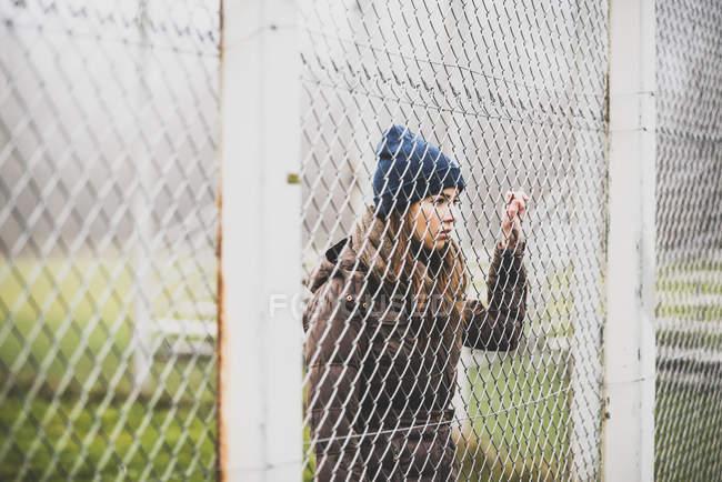 Молодая женщина, стоящая за сеткой ограждения — стоковое фото