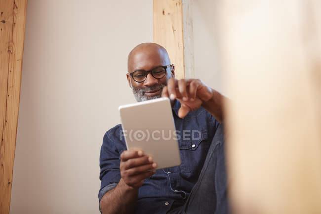 Mann schaut auf digitales Tablet — Stockfoto