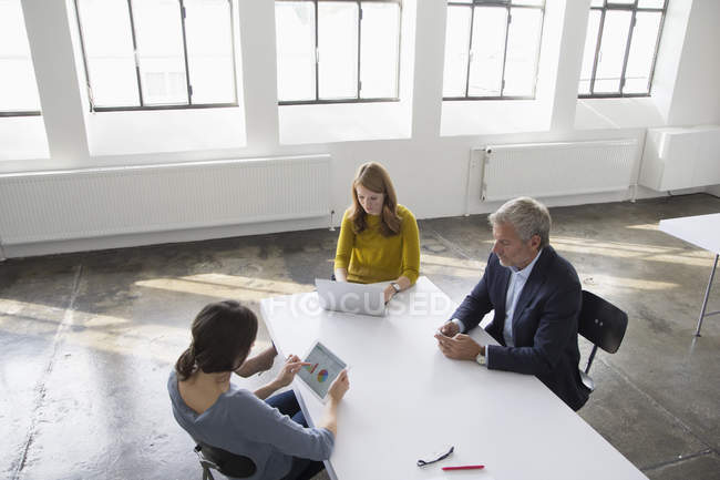 Businessman and two women in conference room using portable devices — Stock Photo