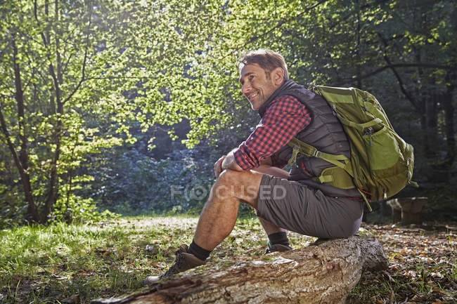 Hiker sitting on tree trunk in forest — Stock Photo