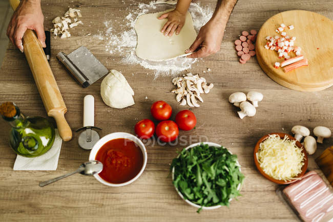 Cropped image of Father and son preparing pizza at home — Stock Photo