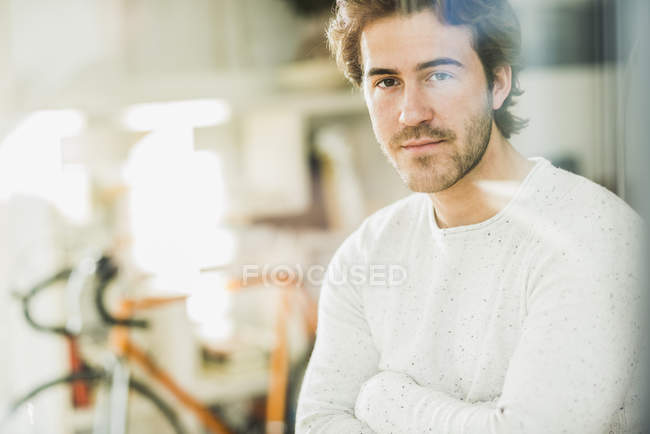 Portrait of young manwith arms crossed looking through windowpane — Stock Photo