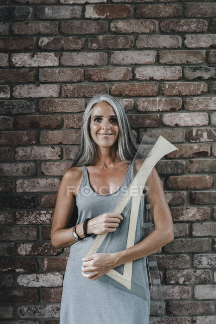 Portrait of woman in front of brick wall holding architectural rulers — Stock Photo