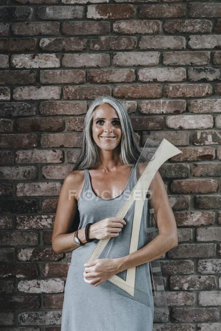 Портрет женщины перед кирпичной стеной с архитектурными правителями — стоковое фото
