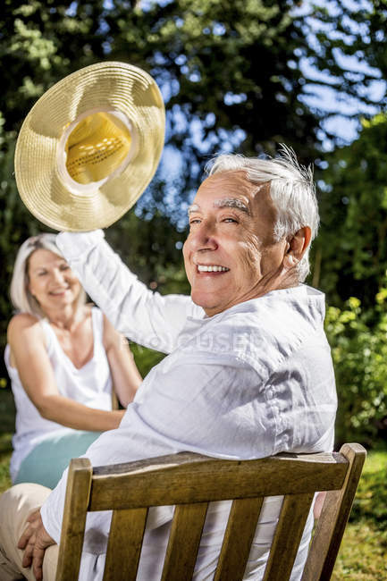 Happy senior man in garden with woman in background — Stock Photo