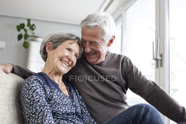 Счастливая старшая пара сидит вместе на диване в гостиной — стоковое фото