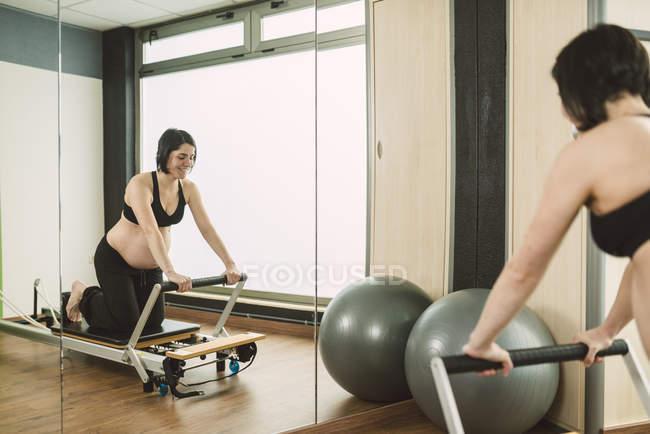 Femme enceinte exercices Pilates dans une salle de sport — Photo de stock