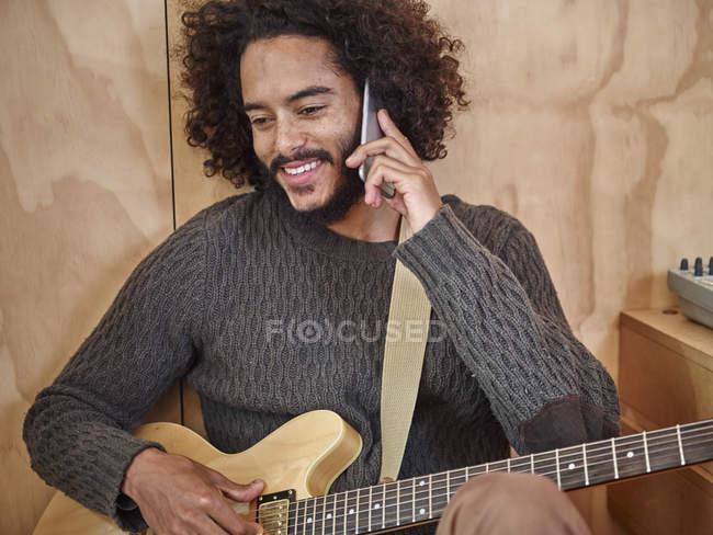 Giovane con chitarra elettrica che parla sul cellulare — Foto stock